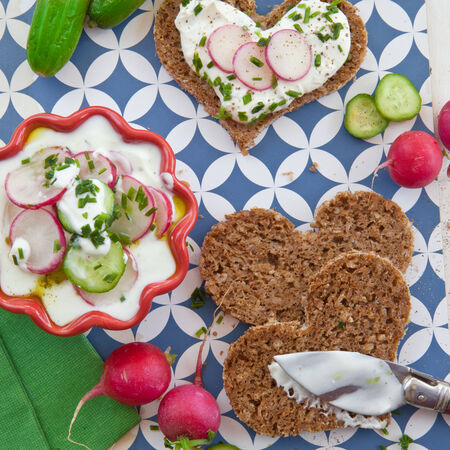 Cream cheese, fresh vegetables, and whole wheat bread photo