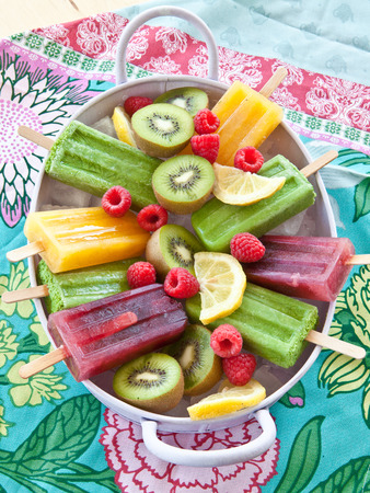 Colorful popsicles with fresh fruits in vintage tray Stock Photo