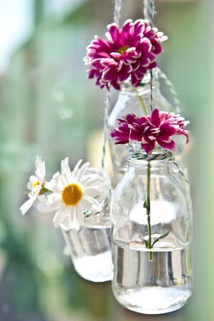 Fresh flowers in little hanging vintage bottles