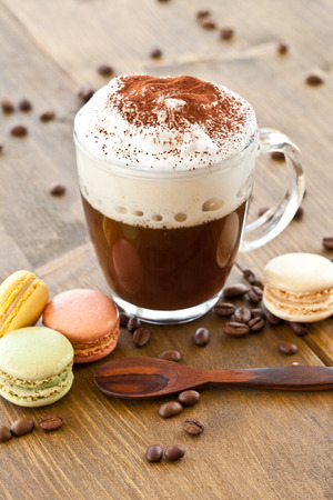 Cup of hot coffee with creamy milk foam and macarons
