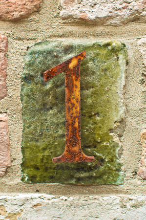 metall: The number one made of rusty metall on a brick wall