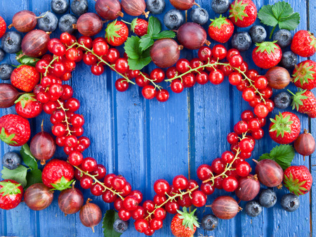 Blue wooden background with fresh summer berries photo
