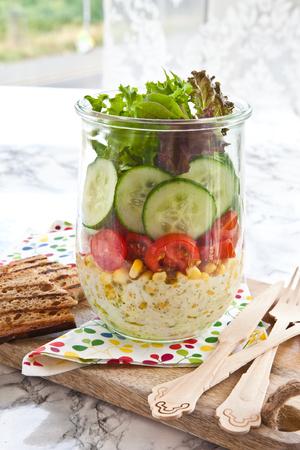 Gelaagde salade met verse groenten in vintage pot