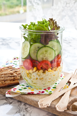 Layered salad with fresh vegetables in vintage jar