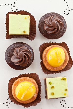 Variety of small cakes with chocolate and orange frosting Stock Photo