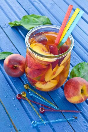 Homemade iced tea with fresh peaches in vintage jar