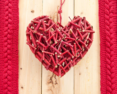 cable stitch: Rustic red heart on wood and knitted ribbon Stock Photo