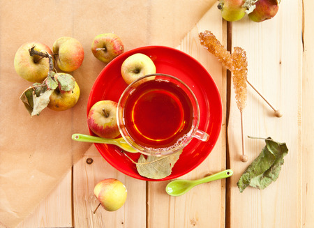 Cup of apple tea on a red plate photo
