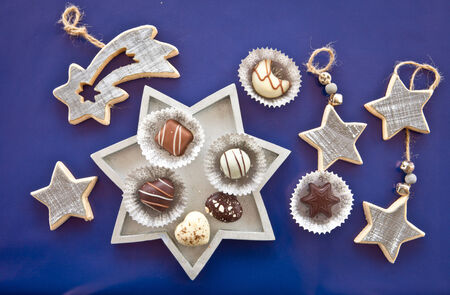 Christmas chocolates and ornaments on blue background photo