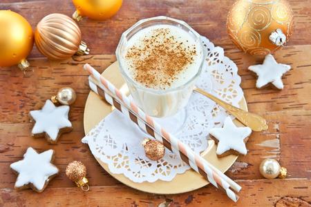 christmas foods: Eggnog with cinnamon  and homemade christmas cookies with sugar frosting