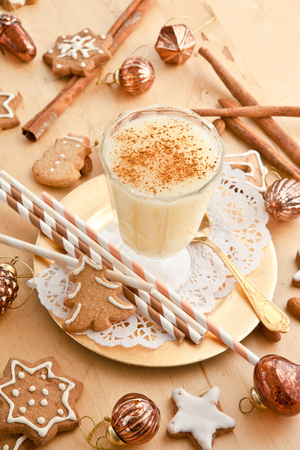 Eggnog with cinnamon  and homemade christmas cookies with sugar frosting photo