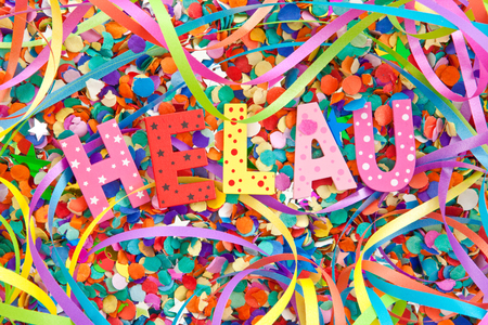 Helau in colorful wooden characters on background made of confetti