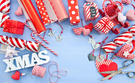 strips away: wrapping prsents for christmas with stripped red and white paper and decorations Stock Photo