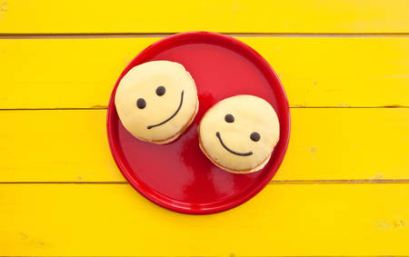 breakfast smiley face: Donut with yellow frosting and a funny smiley face Stock Photo