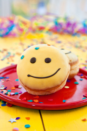 Donut with yellow frosting and a funny smiley face Stock Photo