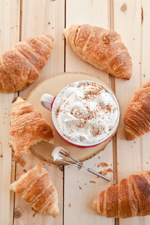 cable knit: Fresh croissants and a big mug with a hot beverage and whipped foam Stock Photo