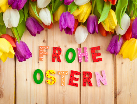 Ostern: Frohe Ostern written in multicolored letters and fresh tulips