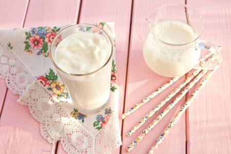 Fresh yogurt in a tall glass on pink wooden boards