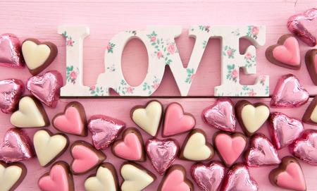 Kleurrijke melk chocolade in hart-vormen op roze