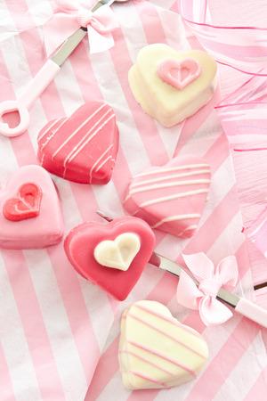 Kleurrijke petit fours in hart vormen op roze Stockfoto