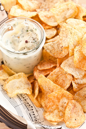 snacking: Homemade potato chips with a glass of mayonaise dip