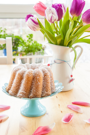 Sponge cake in gugelhupf shape and colorful tulips photo