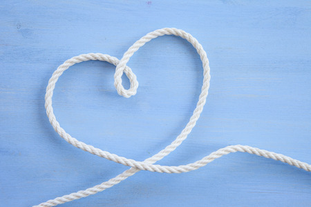 Heart shape made with rope on blue wooden background