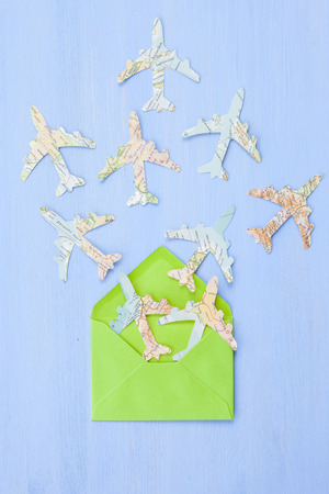 Green envelope with Paper planes made from vintage maps on blue