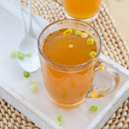 broth: Homemade bone broth with leek in glass cup Stock Photo