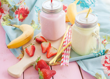 Vintage glass jars with milk and fresh strawberries and bananas