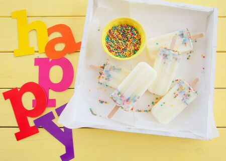 popsicles: Homemade frozen vanilla popsicles with colorful sprinkles Stock Photo