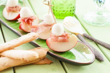Plakken van nectarine met gerookte ham en mozzarella ballen