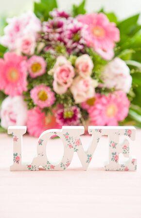 bouquet fleur: Amour dans les lettres en bois en face d'un bouquet de fleurs color� Banque d'images