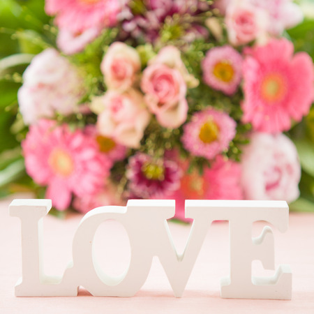 flower bouquet: LOVE in wooden letters in front of a colorful flower bouquet