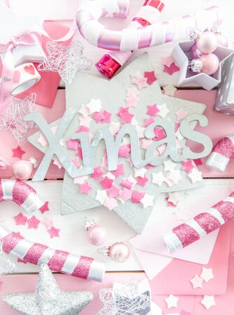 glittery: Pink christmas decorations with glittery ornaments on striped  wooden background Stock Photo