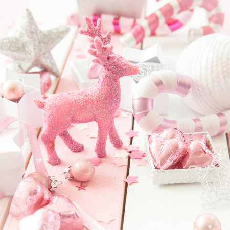 Pink christmas decorations with glittery ornaments on striped  wooden background Stock Photo