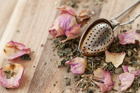 Green tea with pink rose petals with vintage tea spoon