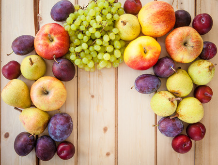 nourish: Fresh autumn fruits on a rustic wooden background