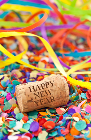 champagne cork: Champagne cork and party streamers on colorful confetti