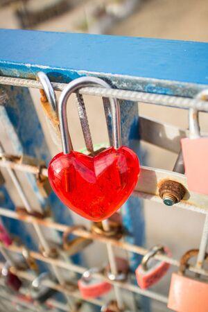 rusty fence: Red padlock in heartshape on rusty fence