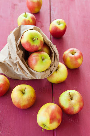 apple paper bag: Fresh ripe apples in paper bag on wooden background Stock Photo
