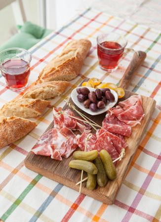 hams: La selección de jamones y salami sobre tabla de cortar de madera de época