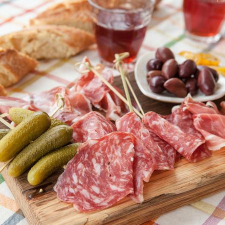 jamones: La selección de jamones y salami sobre tabla de cortar de madera de época