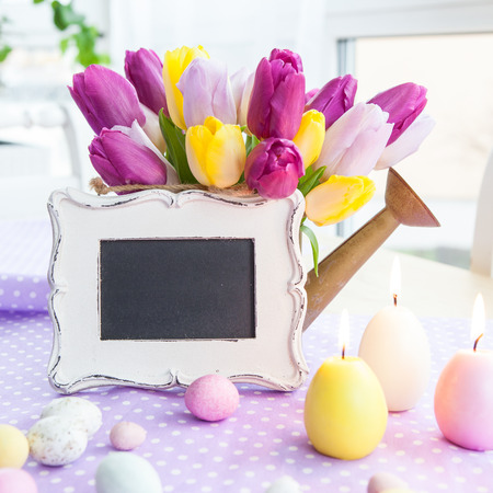 Bouquet of fresh tulips and easter treats on purple background Stockfoto