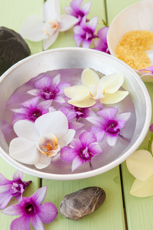 Fresh colorful orchids floating in a bowl of water