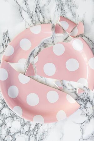 clumsiness: Pink polka dot plate in broken pieces on marbled background