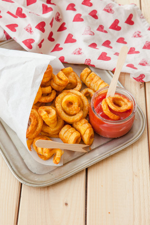 white paper bag: Spicy curly fries in white paper bag Stock Photo