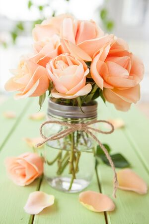 mothersday: Fresh peach roses on rustic wooden background