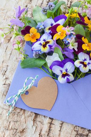 Little bouquet of spring flowers in purple envelope