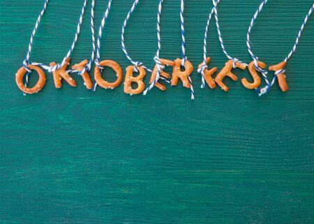 Oktoberfest background with pretzels on rustic dark green wood
